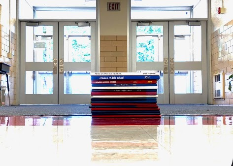 Yearbooks dating back to 1984 stacked in the entrance to symbolize how many people have walked in these halls.